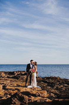 couple stands on rocks, kissing, the ocean behind them