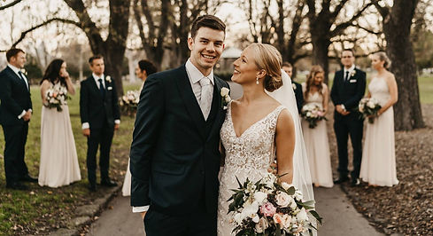 couple stands smiling at each other, their wedding party out of focus behind them