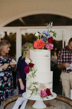 tall two tiered cake covered in red, plum and blue flowers