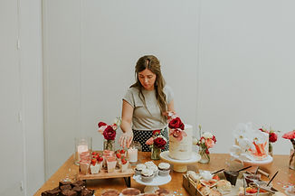 woman lights candle on table filled with cakes and biscuits