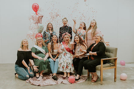 group of women laugh and throw confetti