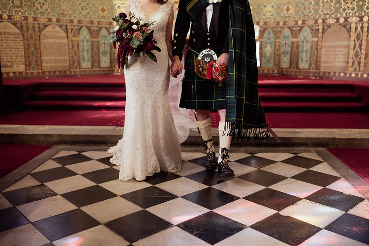 couple stand in chapel holding hands. woman weraing full length white lace and beaded dress, carrying deep red and latte toned bouquet ; man wearing traditional scottish dress