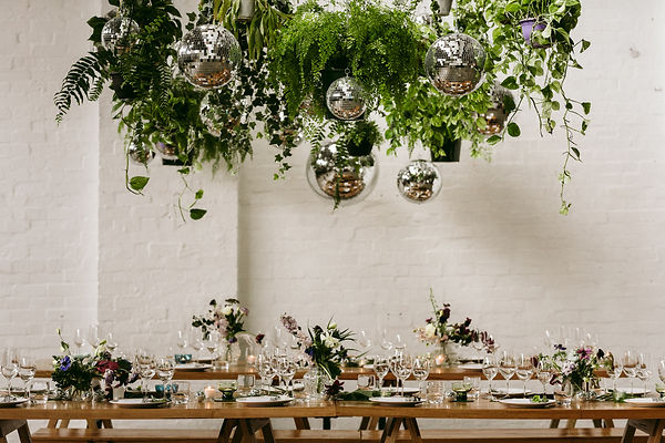 Hanging plants and disco balls hang over a set table