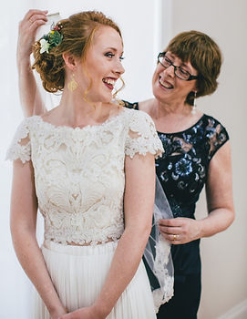 mother helps daughter put on bridal veil