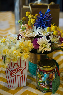 lollies and brightly coloured blooms in popcorn box