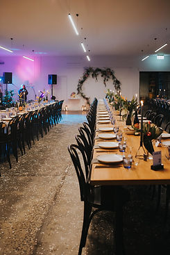 wide shot of reception space - poured concrete floor, black bentwood chairs, tropical blooms and grey taper candles