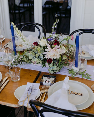 Set table ; white plates, micket mouse shaped cookies, blue taper candles, peach blue and red flowers
