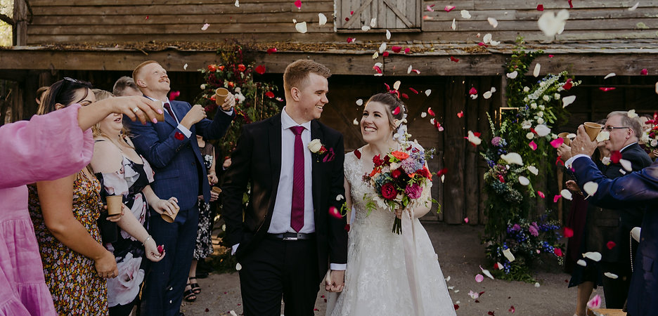 couple smile and laugh walking up the aisle, while their family and friends throw petals around them
