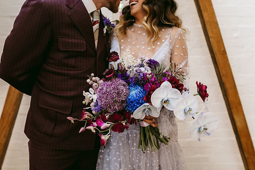 funky couple stand together, bride holds blue purple mauve plum toned bouquet
