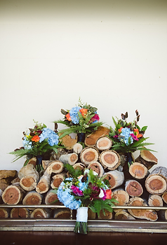 4 bouquets sitting against a wood pile