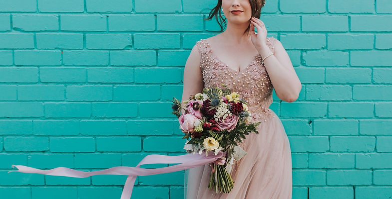 bride wearing light mauve dress stands in front of teal brick wall