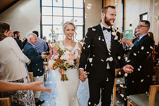 couple walks smiling while petals are thrown around them