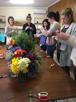 women stand at table making flower crowns