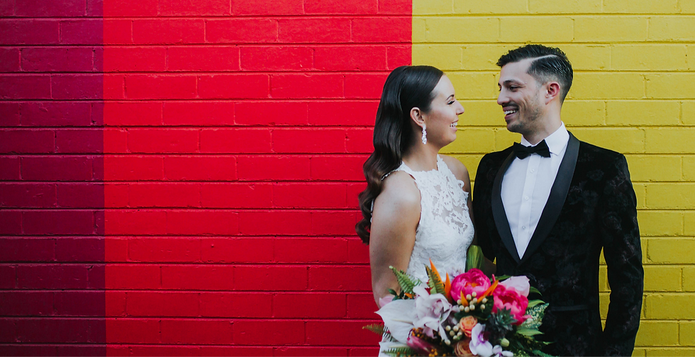 Couple standing in front of brightly coloured wall.