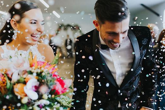 couple laughs as confetti falls around them