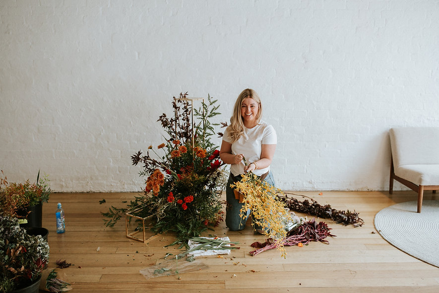 Blonde woman smiling while kneeling on wooden floor, beside a large floral arrangement. She is holding a bunch of yellow orchids.