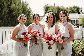 bride and her three bridesmaids hold their bouquets, smiling at the camera