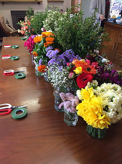 scissors, floral tape and a varierty of flowers on a table