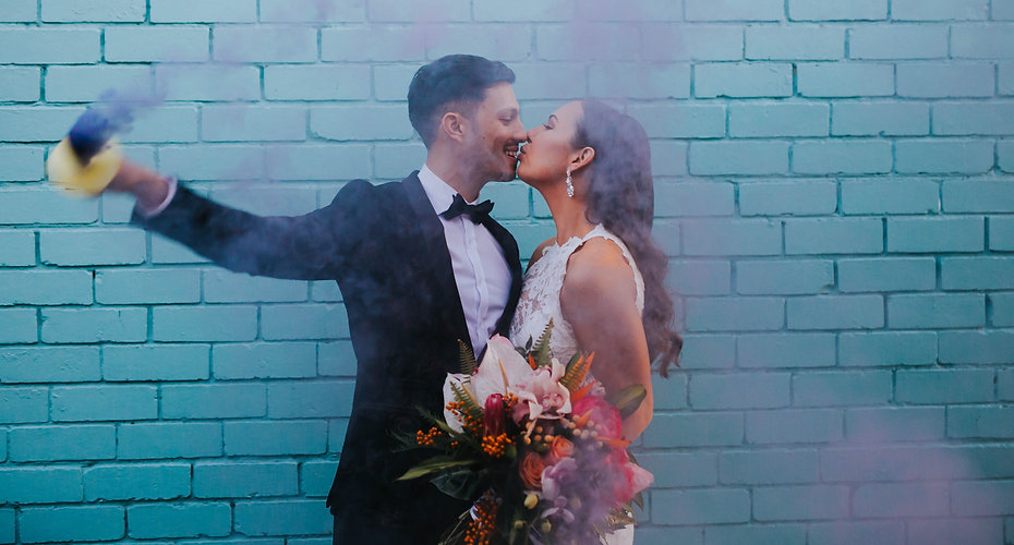 couple hold lips together in front of blue wall, waving blue smoke bomb around