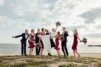 wedding party stand together ; groom carrying bride, bride lifting her bouquet in the air