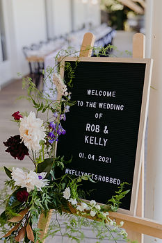 welcome board with floral accent ; board reads 'Welcome to the wedding of Rob & Kelly, 01.04.2021, #KellyGetsRobbed