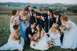 couple crouches and smiles, while their wedding party crowds around them