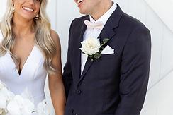 man wears dark navy jacket and white buttonhole