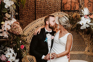Couple share a kiss, both sitting on rattan peacock chair