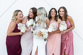 bride and her 4 bridesmaids laugh together