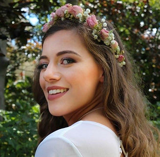 woman smiles, turning to camera, wearing a flower crown
