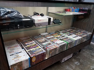 Display case filled with various video games and consoles.