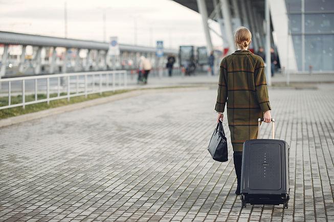 unrecognizable-woman-with-suitcase-walki