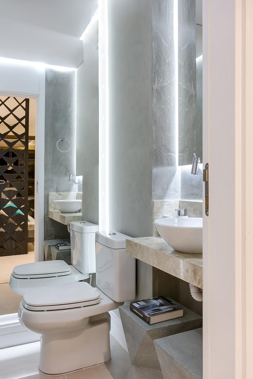 Lavabo com iluminação decorativa atrás dos espelhos