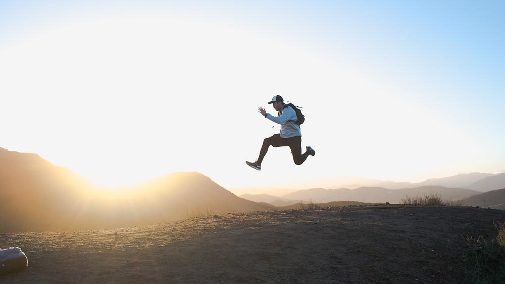 man jumping during mountain hike
