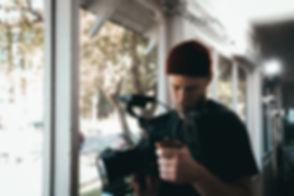 man-carrying-black-video-camera-standing