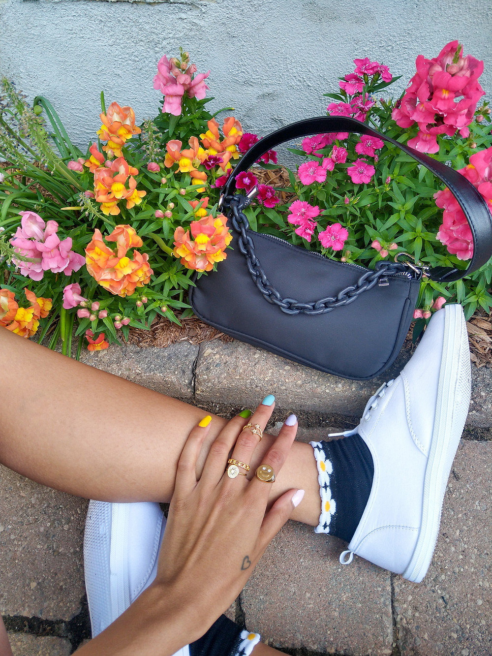 woman wearing gold rings, daisy socks white sneakers