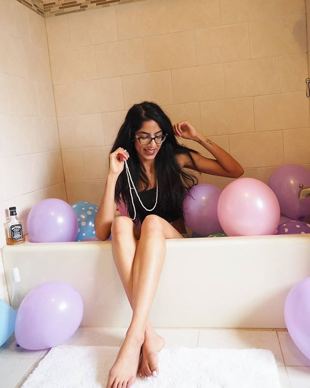 woman in bathtub filled with balloons