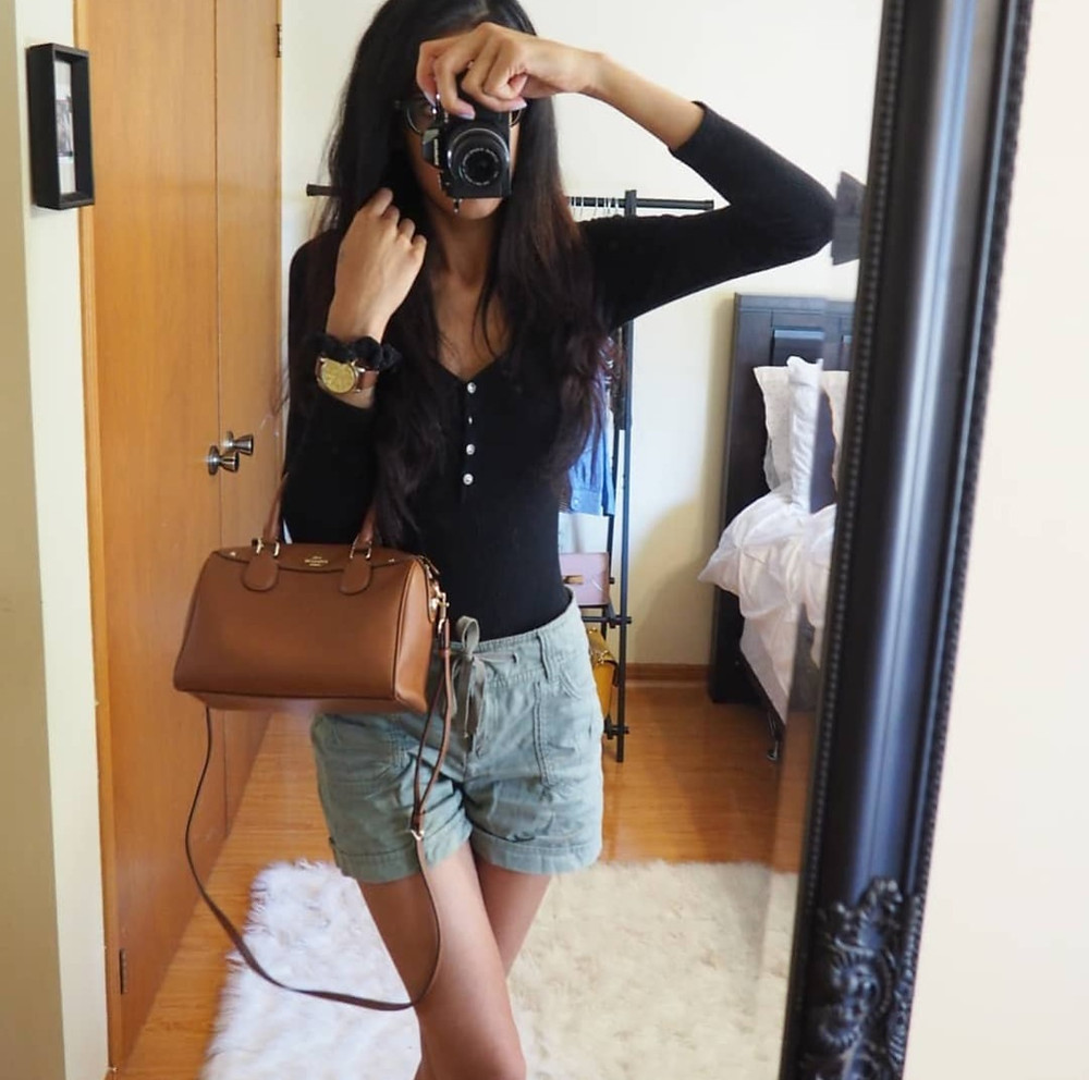 mirror selfie of outfit, shorts brown bag watch and black top