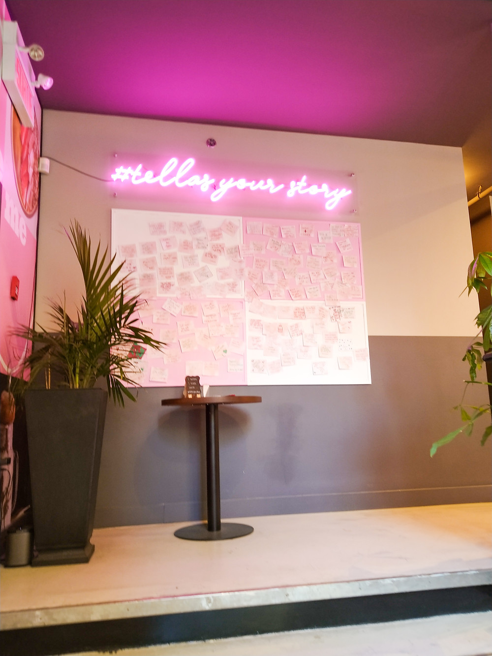 neon sign saying tell us your story - restaurant decor