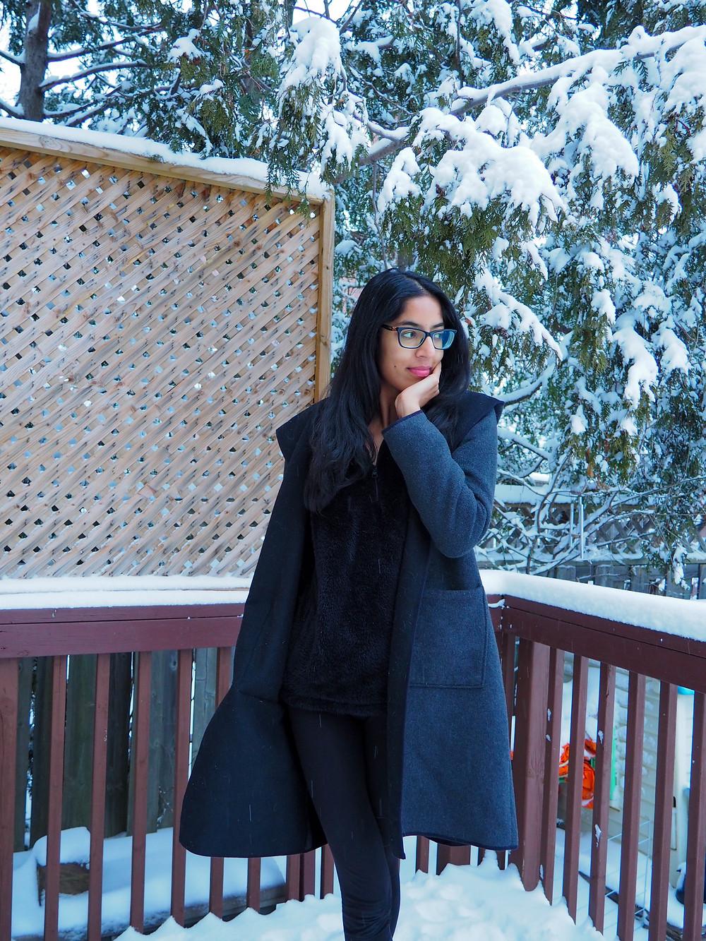 woman standing in snow in coat