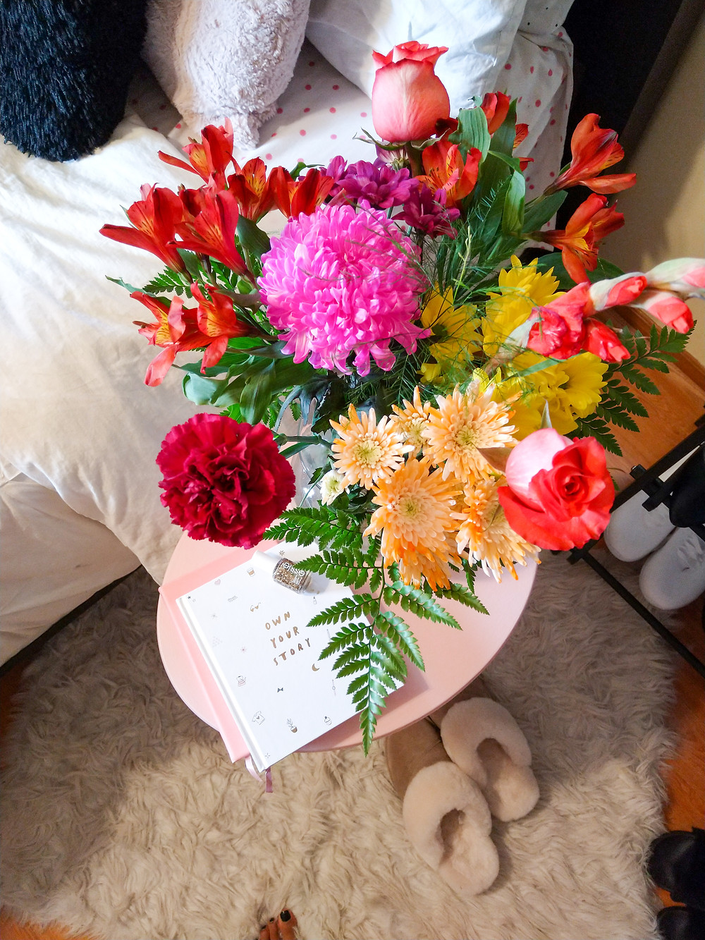 fall flowers by a bed with books and nail polish