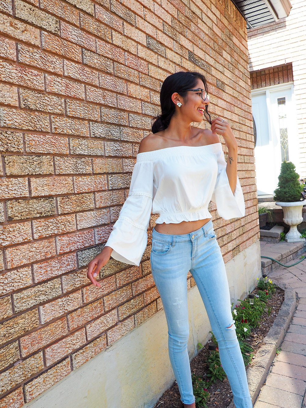 woman with hair in bun wearing white blouse outside of a pink home