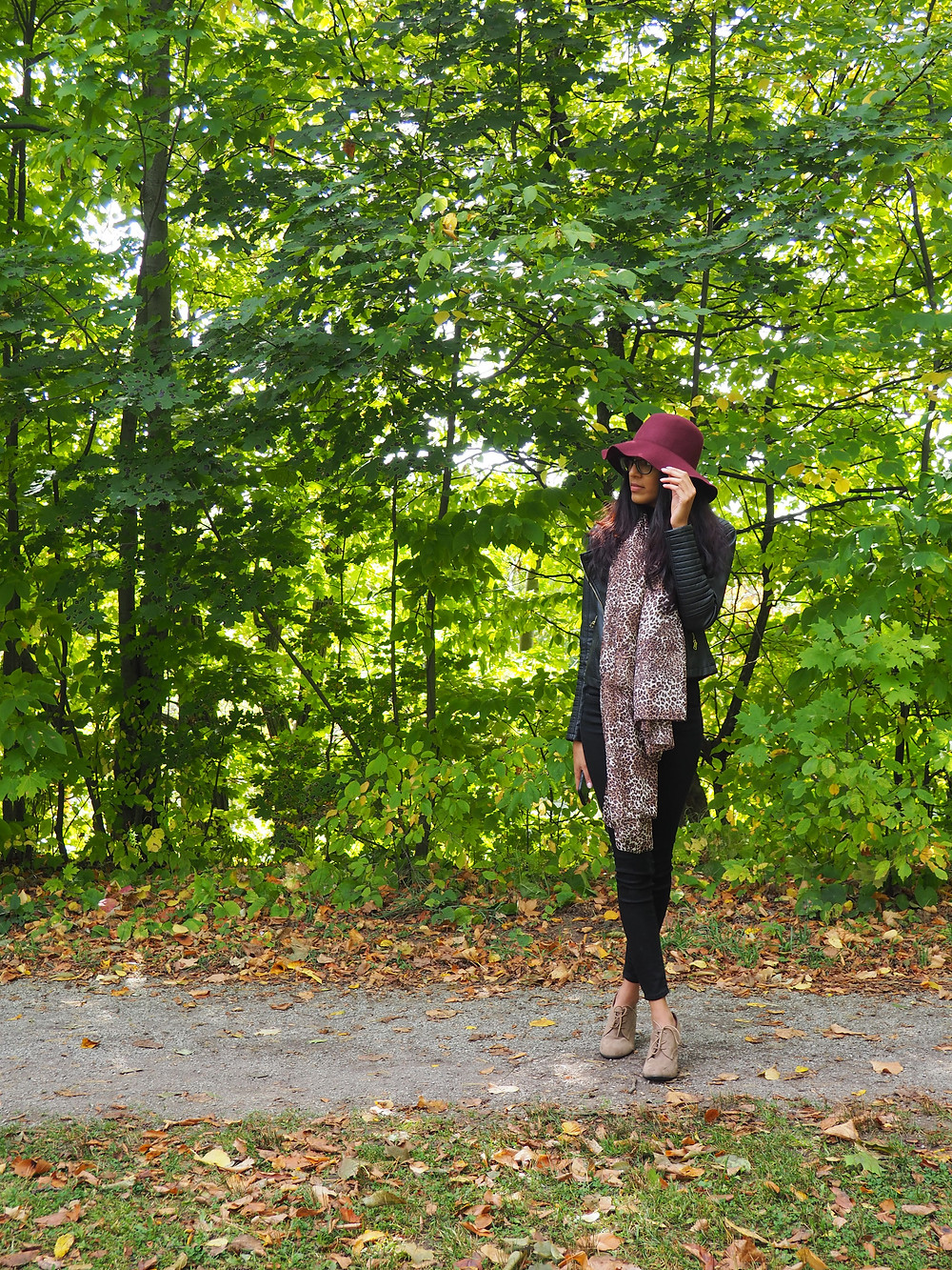woman in woods during fall wearing red hat and scarf. all black outfit and heels