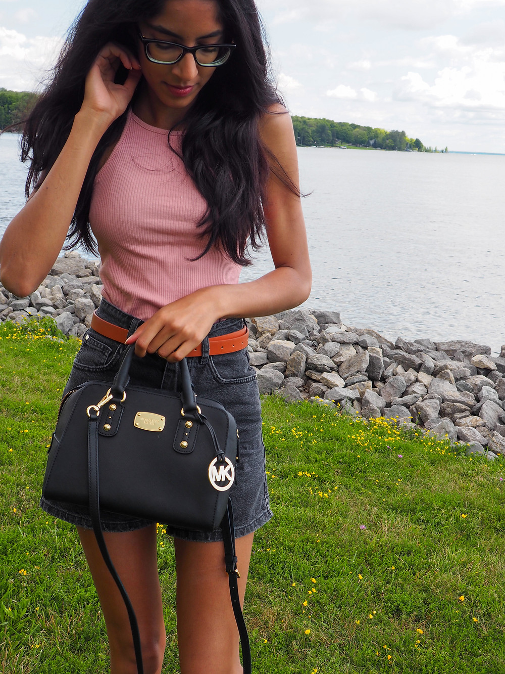 woman walking by water in shorts and tshirt with handbag