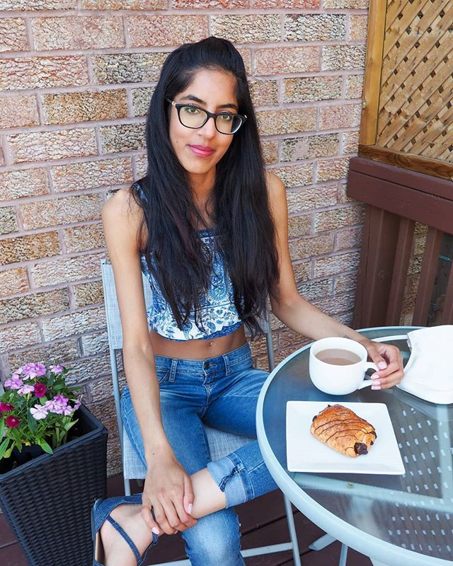 woman sitting at a cafe with dessert and coffee