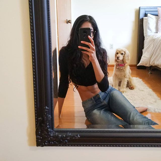 mirror selfie of a woman and her abs with dog in background