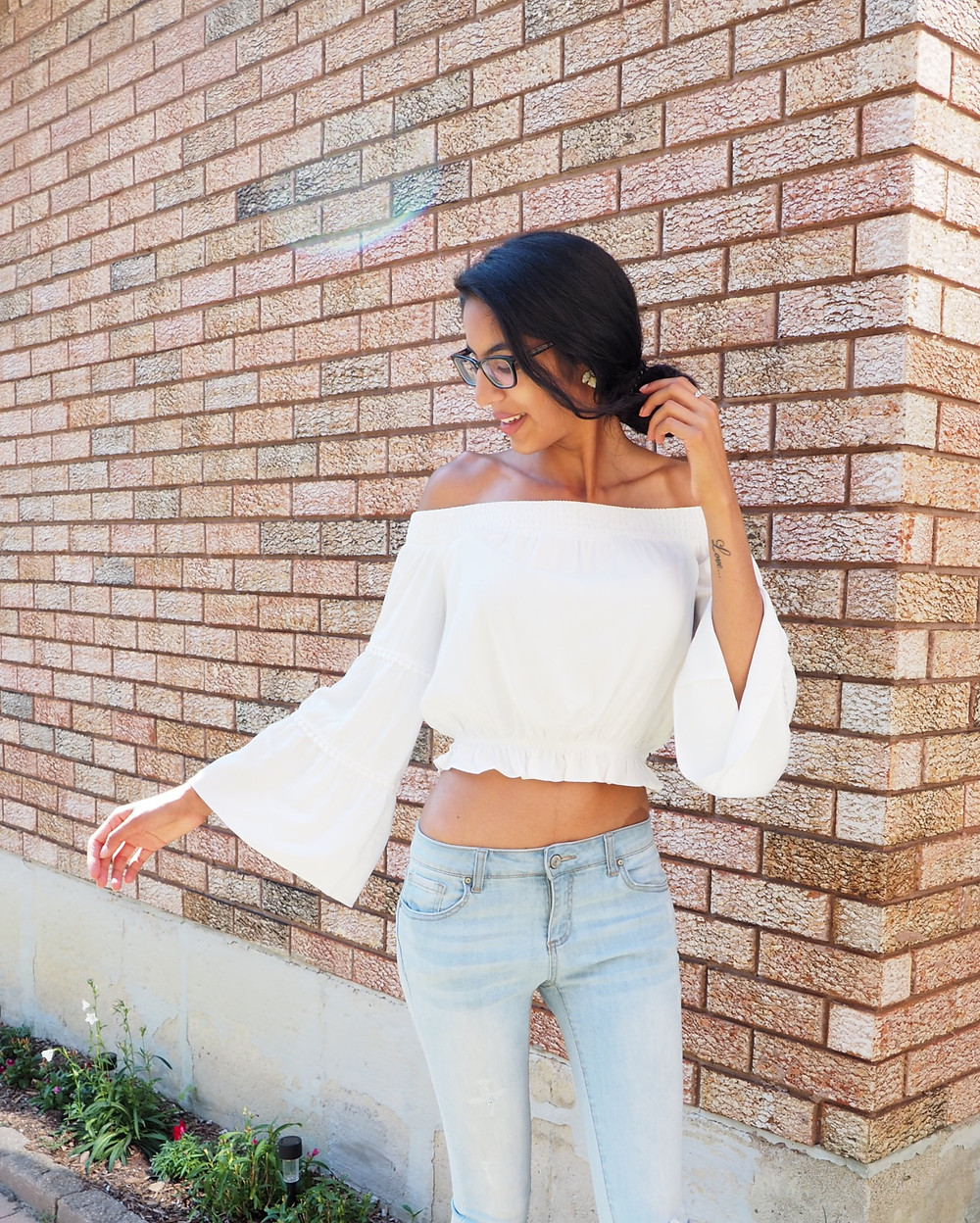 white blouse blue jeans is what a woman is wearing with statement blue earrings