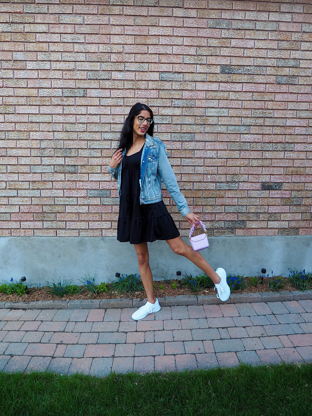 woman in jean jacket dress and sneakers