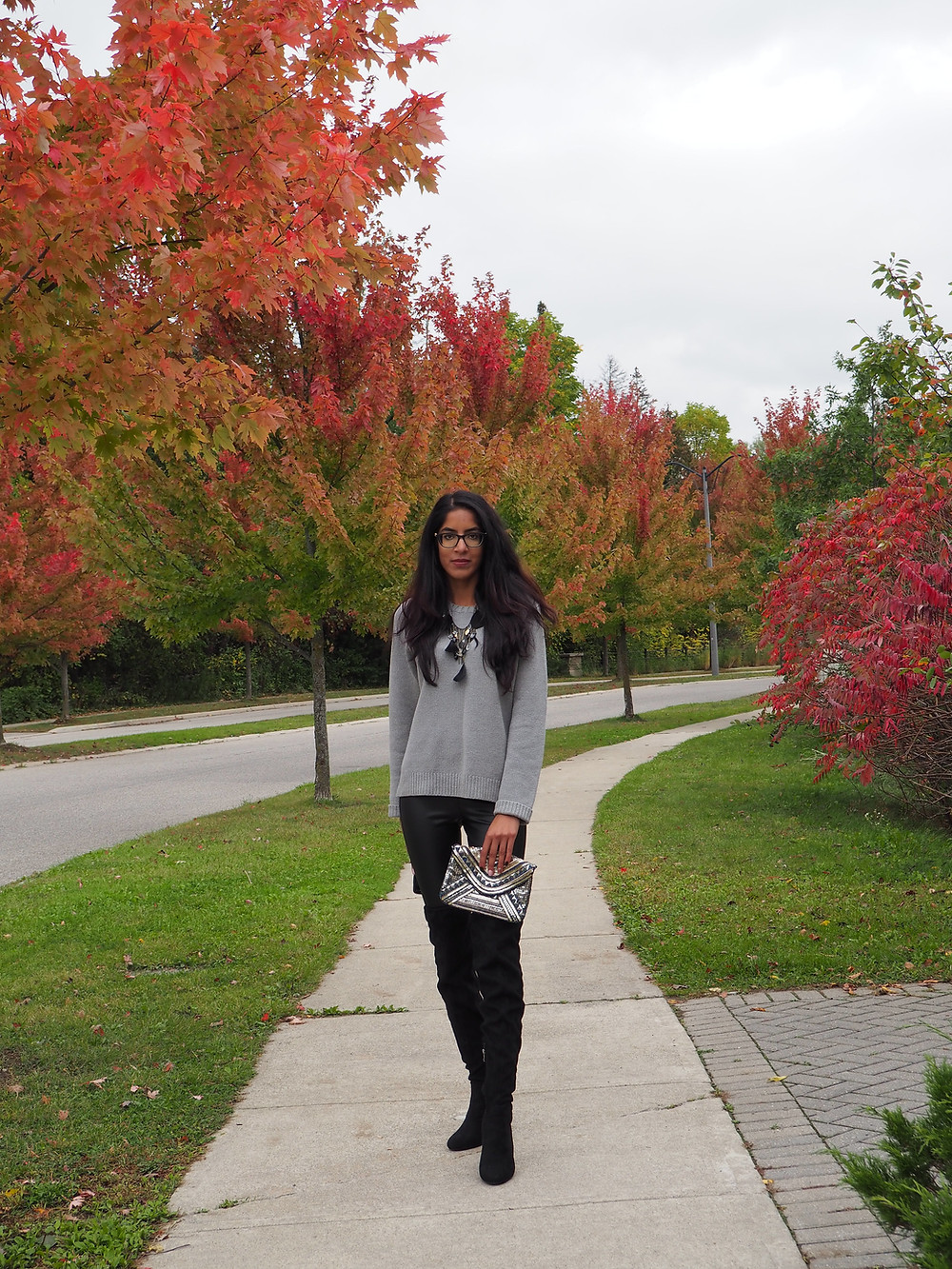 leaves changing colours and woman standing wearing sweater knee high boots