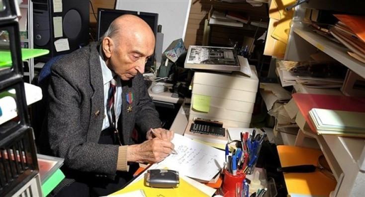 Önümde bir fotoğraf duruyor… Oldukça küçük bir masa.  Kocaman bir büyüteç. Üst üste konmuş kalın kitaplar. Dosyalar. Kağıtlar. Rengarenk kalemler. Masa üstü bir bilgisayar. Bilgisayar kasasına yapıştırılmış küçük not kâğıtları. Mektup zarfları. Ve odaya süzülen gün ışığı. Fotoğrafa bakıyorum.